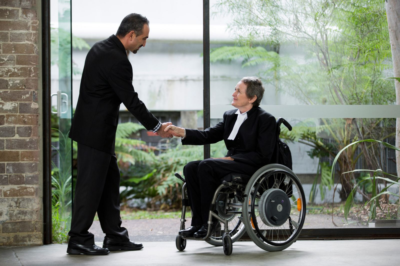 Person in a wheelchair shaking hands with someone