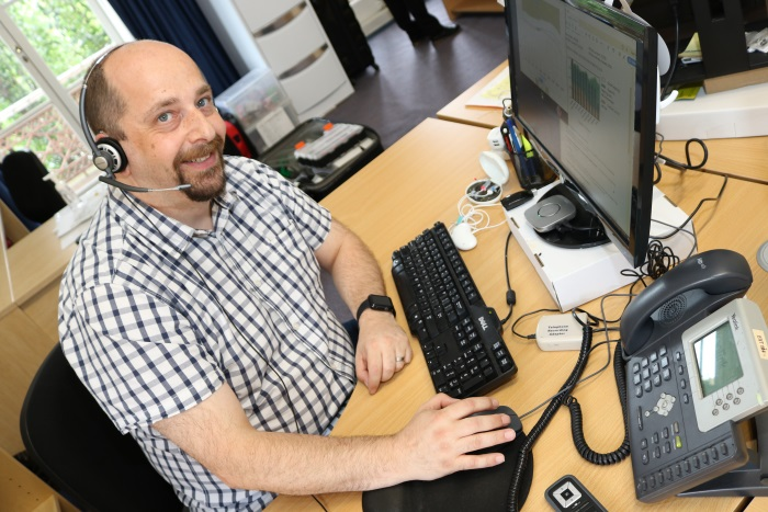 Photo: Daniel Pistritto at his workstation with assistive hearing devices funded by the Employment Assistance Fund (Source: Blamey Saunders hears)